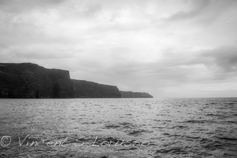 Black and white of the Cliffs of Moher at sea level.